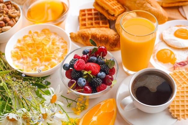 Healthy breakfast set with muesli, fruits, berries, nuts, coffee, eggs, honey, oat grains and more