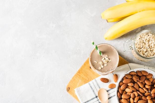 Healthy breakfast smoothie banana oatmeal almond milk on white background