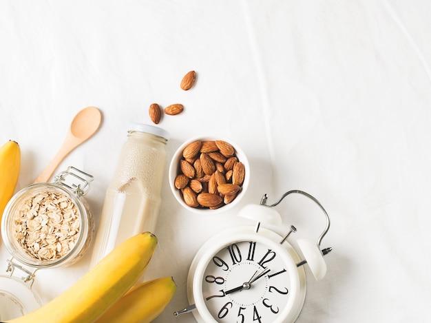 Healthy breakfast smoothie banana oatmeal almond milk with white alarm