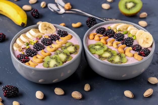 Healthy breakfast smoothie bowl with blackberries, bananas, cashews, kiwi and pistachios, horizontal photo