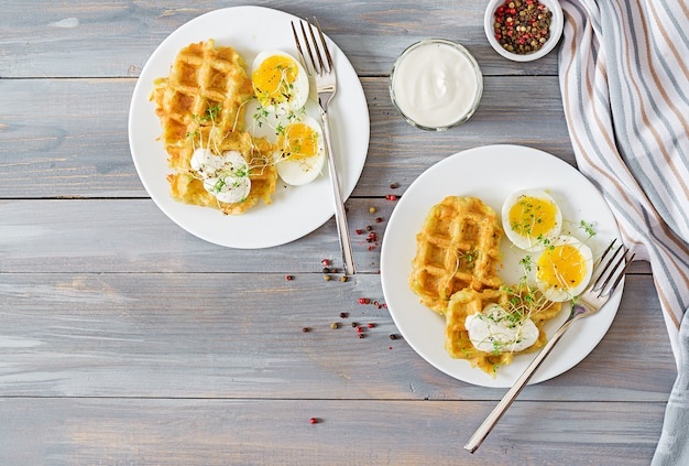 Healthy breakfast or snack. potato waffles and boiled egg on grey wooden table. top view. flat lay