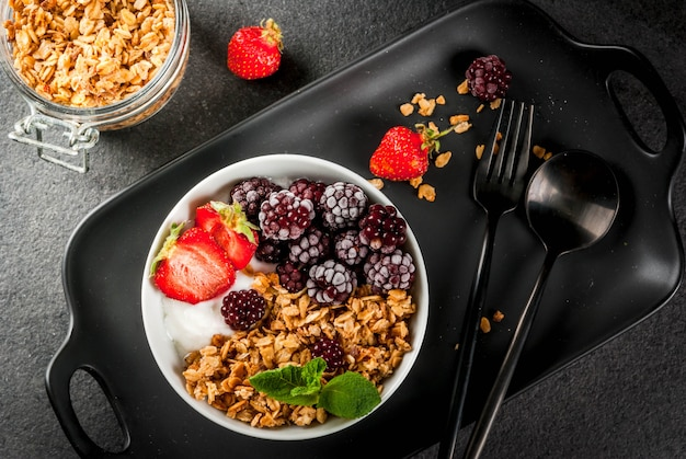 Healthy breakfast. summer berries and fruits. homemade greek yogurt with granola, blackberries, strawberries and mint. on a black stone table, with the ingredients.  top view