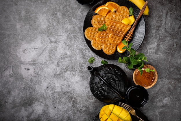 Healthy breakfast surface with fresh hot waffles hearts, pancakes flowers with berry honey and exotic fruits over gray, top view, flat lay. healthy food concept with copy space