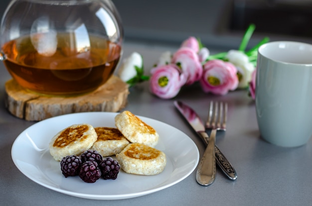 Healthy breakfast table with cheesecakes from cottage cheese with blackberries and glass teapot with green tea.
