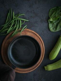 空の調理鍋のモックアップと暗い表面で調理するための材料を備えた健康的な朝食用テーブル上面図コピースペース