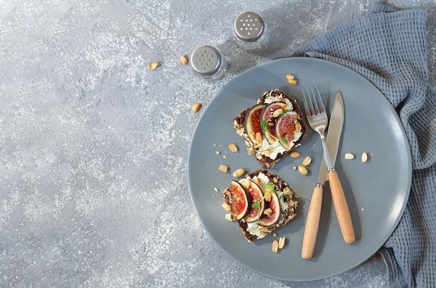 プレート上面図に新鮮なイチジク、クリームチーズ、ナッツ、スパイスを使ったヘルシーな朝食トースト