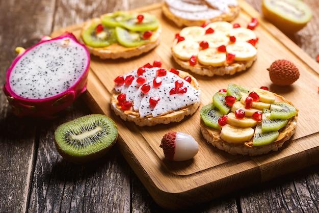 Healthy breakfast toasts with peanut butter, banana, kiwi, dragon fruit, pomegranate and lychee.