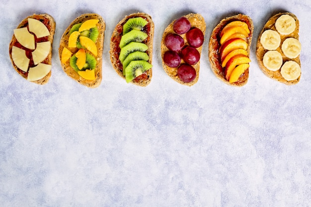 Healthy breakfast toasts with peanut butter, strawberry jam, banana, grapes, peach, kiwi, pineapple, nuts. copy space
