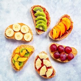 Здоровые завтраки подаются с арахисовым маслом, клубничным джемом, бананом, виноградом, персиком, киви, ананасом, орехами. копировать пространство