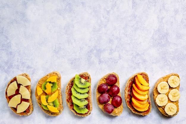 Здоровые тосты на завтрак с арахисовым маслом, клубничным джемом, фруктами