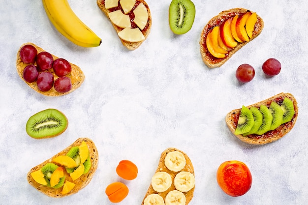 Healthy breakfast toasts with peanut butter, strawberry jam, fruits