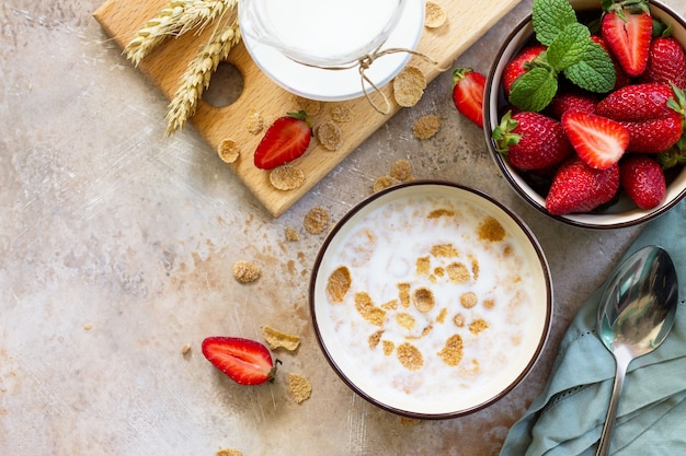 健康的な朝食全粒粉フレークミルクと石の背景に新鮮なイチゴコピースペース