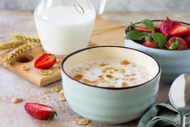 石またはスレートの背景に健康的な朝食全粒フレークミルクと新鮮なイチゴ
