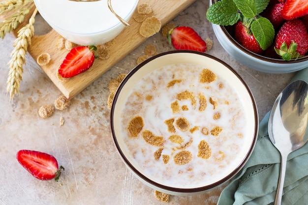 건강한 아침 식사 통 곡물은 우유와 신선한 딸기를 돌이나 슬레이트에 뿌립니다.