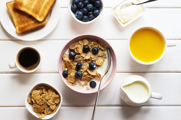 Healthy breakfast of whole wheat flakes with milk blueberries cup of coffee orange juice and toast on white wooden table