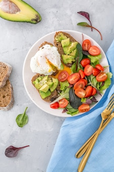 Healthy breakfast with avocado toasts, poached egg and salad