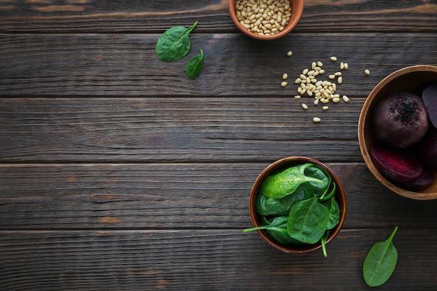 삶은 비트 뿌리, 아기 시금치 잎, 어두운 나무 테이블에 잣으로 건강 한 아침 식사. 평면도