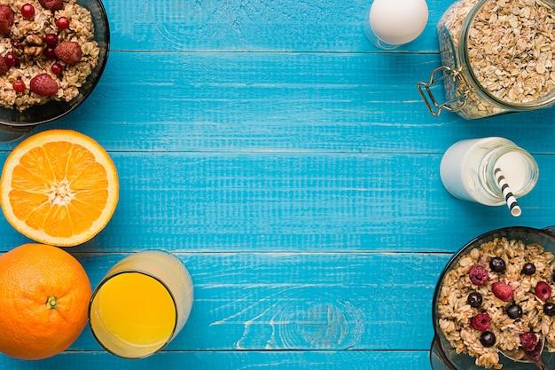 소박한 나무 배경 위에 딸기와 오렌지 주스를 곁들인 홈메이드 오트밀 한 그릇이 포함된 건강한 아침 식사. 평면도. 정물. 복사 공간