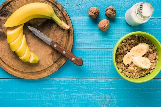 소박한 나무 배경 위에 과일과 우유를 곁들인 홈메이드 오트밀 한 그릇으로 구성된 건강한 아침 식사. 정물. 복사 공간