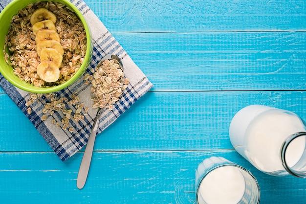 소박한 나무 배경 위에 과일과 우유를 곁들인 홈메이드 오트밀 한 그릇으로 구성된 건강한 조식
