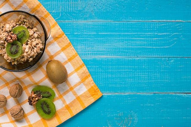 소박한 나무 배경 위에 키위와 견과류를 곁들인 홈메이드 오트밀 한 그릇으로 구성된 건강한 아침 식사. 정물. 복사 공간