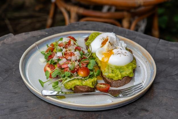 Здоровый завтрак с хлебными тостами и яйцом-пашот с зеленым салатом, красными помидорами и разбитым авокадо