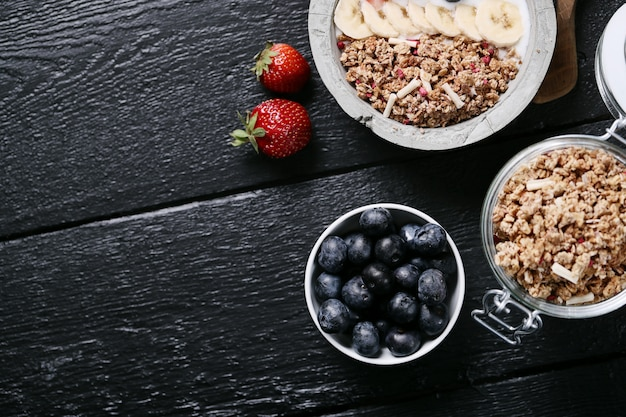 Healthy breakfast with cereals and fruits on black wooden table