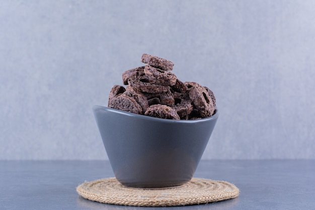 石の上の黒いボウルにチョコレートコーンリングを入れたヘルシーな朝食。