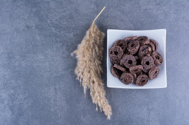 Prima colazione sana con anelli di mais al cioccolato in un piatto su una superficie di pietra