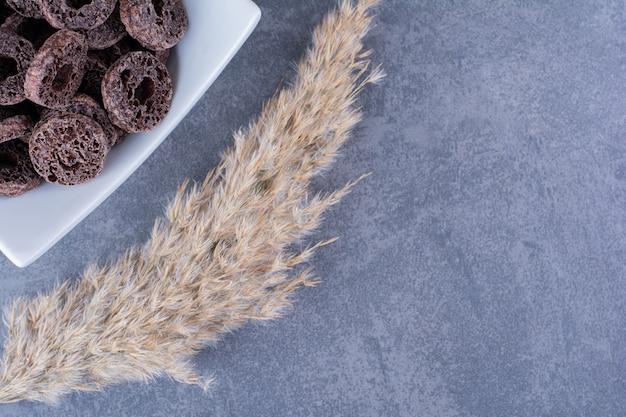 Sana colazione con anelli di mais al cioccolato in un piatto su una pietra.
