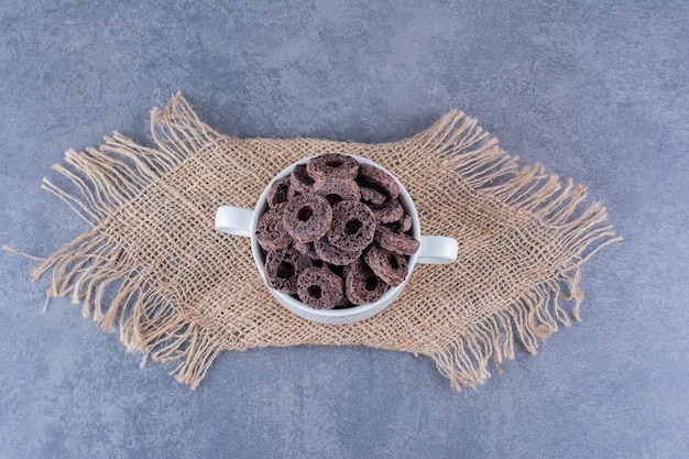 Healthy breakfast with chocolate corn rings in a plate on a stone.