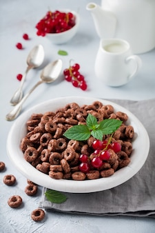 Healthy breakfast with chocolate corn rings, red currant berries, yogurt and tea on a gray concrete background