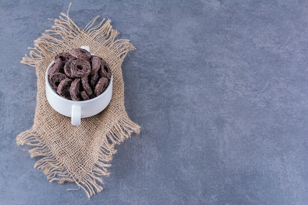 Healthy breakfast with chocolate corn rings in a white bowl on stone.