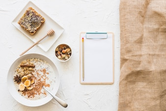 Healthy breakfast with clipboard and pencil on white backdrop
