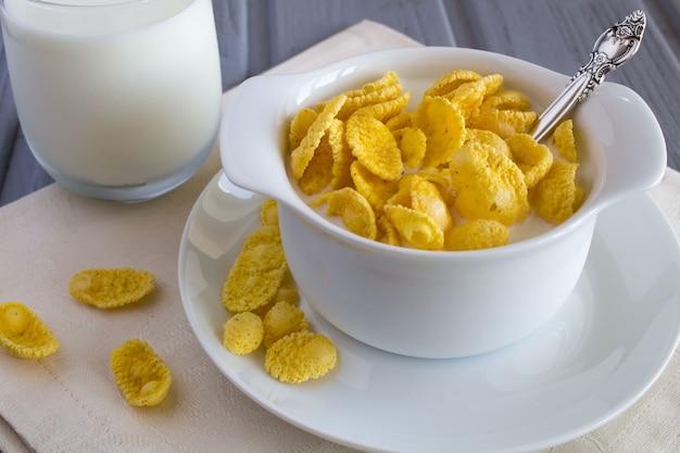 白いプレートにコーンフレークと牛乳を入れたヘルシーな朝食