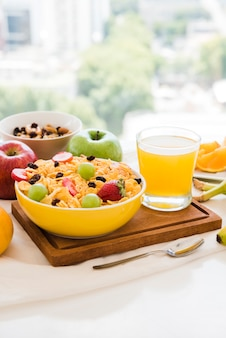 Healthy breakfast with cornflakes; dried fruits; apple and juice glass on table