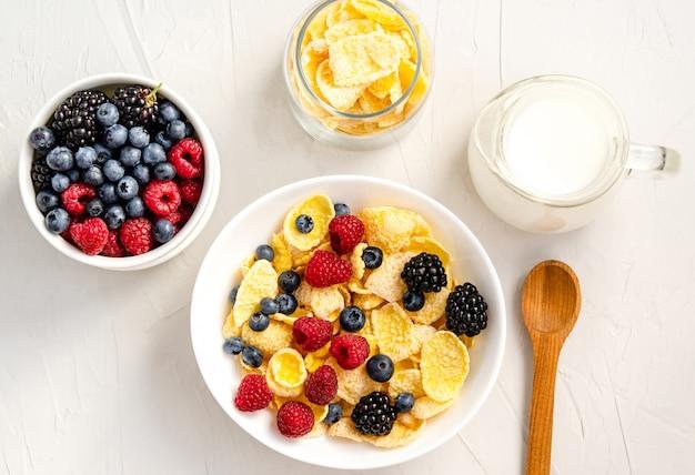 Здоровый завтрак с кукурузными хлопьями, малиной, ежевикой, черникой, молоком и кофе на белой поверхности