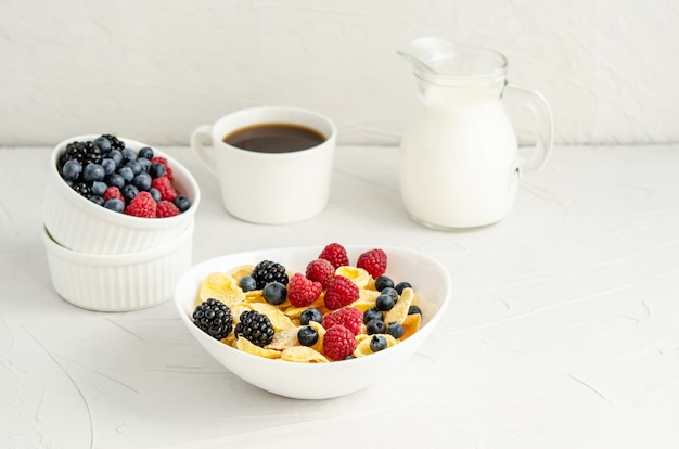 Healthy breakfast with cornflakes, raspberries, blackberries, blueberries, milk and coffee on a white surface