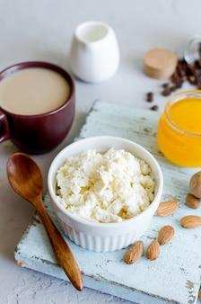 Здоровый завтрак с творогом или рикоттой с миндальными орехами, медом и чашкой кофе
