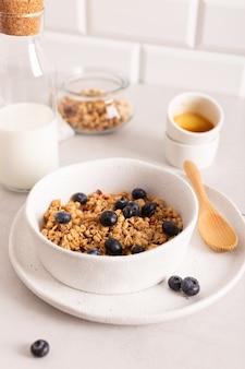 白いボウルにブルーベリーとカリカリのグラノーラと健康的な朝食