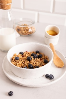 Healthy breakfast with crunchy granola with blueberries in a white bowl