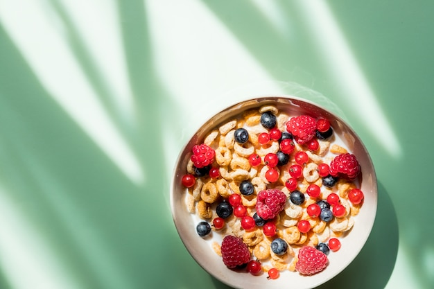 Healthy breakfast with flakes and fruits isolated on green background.