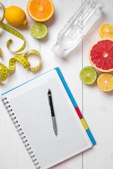 소박한 나무 테이블에 노트북과 함께 신선한 과일과 물 한 병으로 구성된 건강한 아침 식사