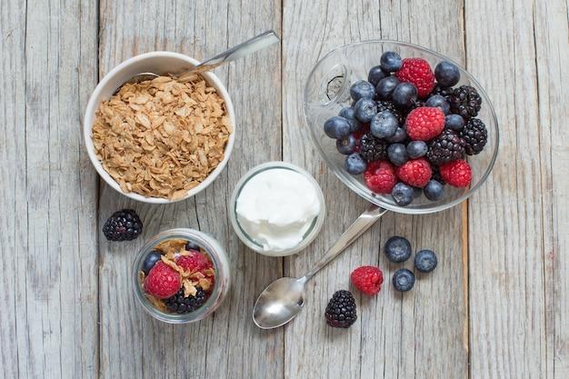 Здоровый завтрак со свежим греческим йогуртом, хлопьями и ягодами на дереве