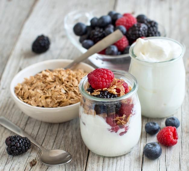 Здоровый завтрак со свежим греческим йогуртом, хлопьями и ягодами