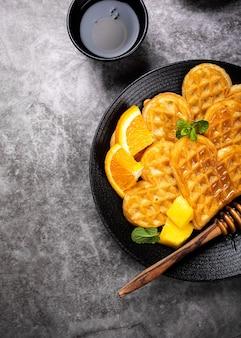 新鮮なホットワッフルの心、ベリーの蜂蜜とエキゾチックなフルーツと灰色の表面、上面図、フラットレイとパンケーキの花と健康的な朝食。食品のコンセプト