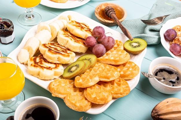 Здоровый завтрак с сердечками свежих горячих вафель, цветами блинов с ягодным вареньем и фруктами на бирюзовой поверхности, вид сверху, плоская планировка. концепция питания