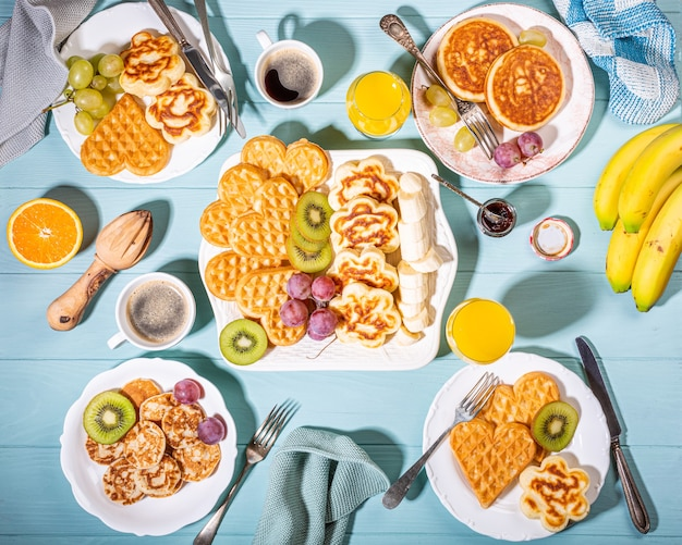 Healthy breakfast with fresh hot waffles hearts, pancakes flowers with berry jam and fruits on turquoise surface, top view, flat lay. food concept
