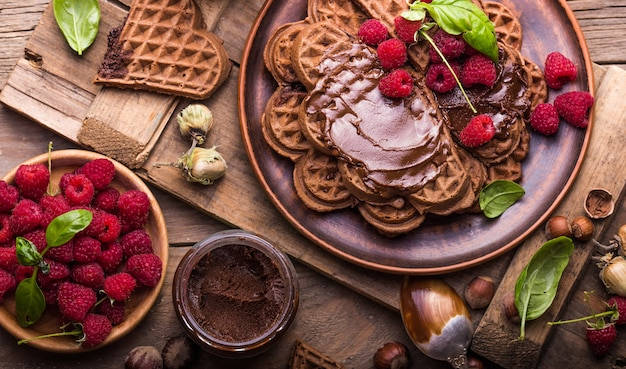 Healthy breakfast with fresh hot waffles hearts, pancakes  with chocolate cream and raspberry