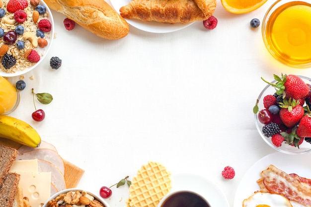 Healthy breakfast with fruits, berries, nuts, coffee, eggs, honey and grains on white background